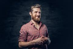 Бородатый мужчина одетый в красной рубашке ватки делает переговор стоковая фотография rf