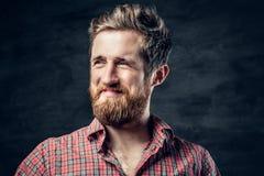 Бородатый мужчина одетый в красной рубашке ватки делает переговор стоковые изображения