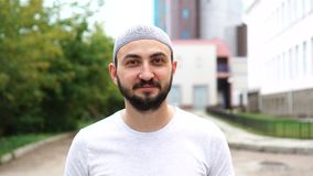 Бородатый мусульманский человек в городе смотря камеру видеоматериал