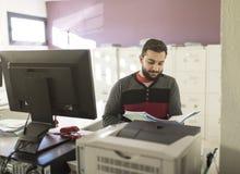 Бородатый офис человека смотря некоторые файлы работая в после полудня Стоковое фото RF