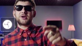 Бородатый парень говорит и динамически хлопает в комнате с загоренным акции видеоматериалы