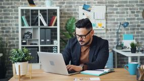 Бородатый парень используя ноутбук на работе после этого писать информацию в тетради акции видеоматериалы