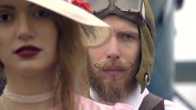 Бородатый пилот стоит за женщиной в розовом платье и белой шляпе в ретро стиле на фоне видеоматериал