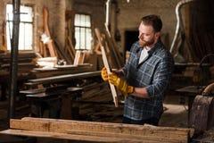 бородатый плотник в защитных перчатках работая с древесиной стоковое фото rf