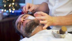 Бородатый побритый человек получая стрижку бороды и сток-видео