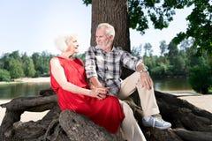 Бородатый пожилой человек нося бежевые брюки и тапки сидя около жены стоковая фотография