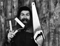 Бородатый построитель держа различные инструменты здания с счастливой стороной Стоковое Изображение