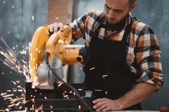 Бородатый сильный механик используя электрический угловой шлифовальный станок на фабрике, искрах летает врозь Незавершенная работ стоковое изображение