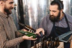 Бородатый специалист по винзавода выбирает бутылку для следующий разливать по бутылкам пива на винзаводе ремесла Стоковые Фотографии RF