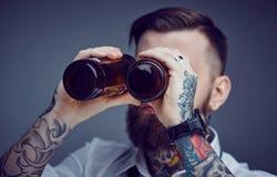 Бородатый татуированный человек смотря через bootles пива Стоковые Изображения RF