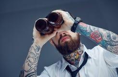 Бородатый татуированный человек смотря через bootles пива Стоковое фото RF