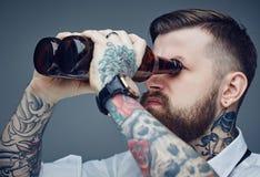 Бородатый татуированный человек смотря через bootles пива Стоковое Изображение