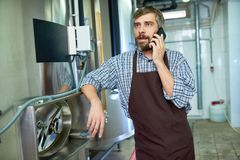 Бородатый техник используя мобильный телефон стоковое фото