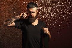 Бородатый усик twirl человека с бутылкой на предпосылке bokeh стоковое фото