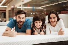 Бородатый человек, вместе с его красивыми женой и сыном, ослабляет на тюфяке в магазине Стоковое Изображение