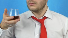 Бородатый человек в белых рубашке и связи держа стекло с алкоголем и смотря его, конец-вверх, голубую предпосылку видеоматериал