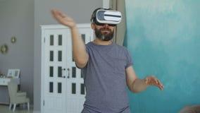 Бородатый человек в вскользь одеждах использует стекла виртуальной реальности и показывать пока стоящ в его квартире самомоднейше видеоматериал
