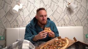 Бородатый человек в зеленом купальном халате в спальне на кровати съесть пиццу для того чтобы насладиться ей замедленное движение видеоматериал