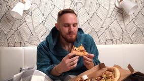 Бородатый человек в зеленом купальном халате в спальне на кровати съесть пиццу и насладиться ее видеоматериал