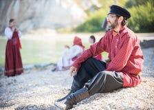 Бородатый человек в русском национальном костюме сидит на предпосылке изумительного ландшафта стоковые изображения rf