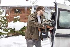 Бородатый человек в стеклах кладет вещи в хобот автомобиля, agains стоковая фотография rf