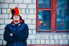 Бородатый человек в шляпе скомороха стоит около кирпичной стены стоковые изображения rf