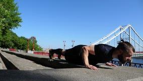 Бородатый человек делает нажимает вверх тренировки около моста Внешняя тренировка фитнеса видеоматериал
