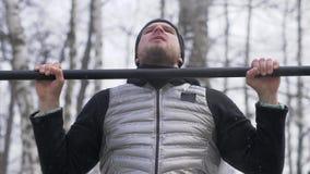 Бородатый человек делая тягу вверх по тренировке во время внешней тренировки на земле спорта стоковое фото rf