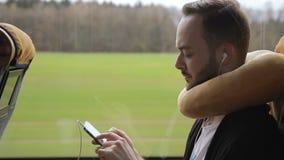 Бородатый человек едет шина, держа smartphone и слушая к музыке на наушниках акции видеоматериалы