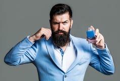 Бородатый человек задерживая бутылку духов Бутылка кёльна моды Бородатый мужчина предпочитает дорогой запах благоуханием человек стоковое фото