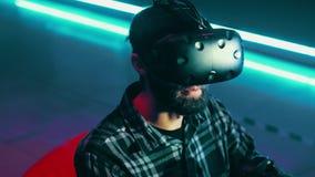 Бородатый человек используя современный шлемофон виртуальной реальности с gamepad, играя игру vr акции видеоматериалы
