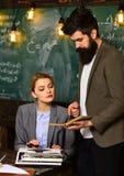 Бородатый человек и чувственная женщина прочитали книгу Работа бизнесмена с секретаршей женщины в школьном офисе Пары с машинкой Стоковое Изображение