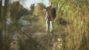 Бородатый человек приблиубежит к камера и взгляды на воде Штанга зафиксирована в особенной ручке на речном береге сток-видео