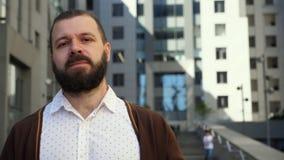 Бородатый человек принимает его стекла Человек стоит перед деловым центром Бизнесмен удовлетворяется с результатом h сток-видео