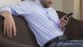Бородатый человек сидя на софе и перечисляя smartphone, социальные сети, устройство сток-видео