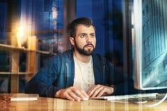 Бородатый человек смотря внимательно на экране пока работающ самостоятельно Стоковые Изображения