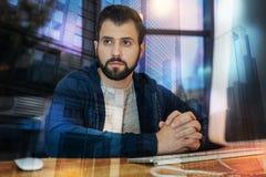 Бородатый человек смотря в расстояние пока сидящ самостоятельно Стоковое Изображение RF