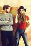 Бородатый человек смотря черную шляпу милой девушки нося стоковые фотографии rf