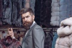 Бородатый человек среди меха, роскоши, moneybags, дела стоковые фотографии rf