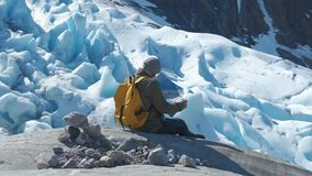 Бородатый человек с желтым рюкзаком и туристская карта в его руках, против фона ландшафта зимы сток-видео