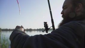 Бородатый человек удит на речном береге Мужчина пробует получить рыб, но они избегают Рыбная ловля реки видеоматериал