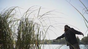 Бородатый человек удит на речном береге Рыболов с рыболовной удочкой на реке Рыбная ловля реки движение медленное сток-видео