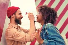 Бородатый человек усмехаясь и держа красные стекла его жизнерадостной подруги стоковые изображения rf