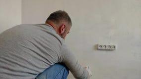 бородатый человек 4K крася внутренние стены на квартире используя кисть Красивый молодой человек делая ремонты - активно красит сток-видео