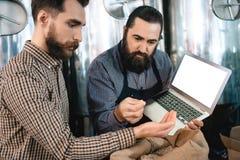 2 бородатых люд проверяют качество солода ячменя пока в винзаводе Процесс производства пива Стоковая Фотография RF