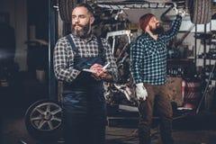 2 бородатых люд ремонтируя автомобиль в гараже Стоковые Изображения