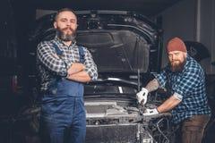 2 бородатых люд ремонтируя автомобиль в гараже Стоковое Изображение