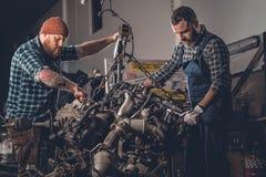 2 бородатых люд ремонтируя автомобиль в гараже Стоковое фото RF