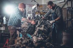 2 бородатых люд ремонтируя автомобиль в гараже Стоковые Изображения RF