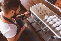 Бородатое barista работая перед машиной кофе Стоковые Фотографии RF